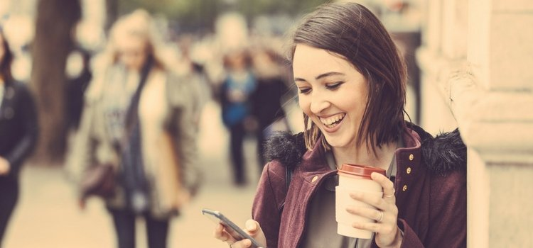 Image of woman holding and reading phone