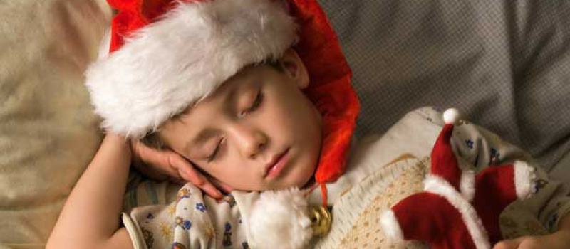 Image of child sleeping with Christmas hat on