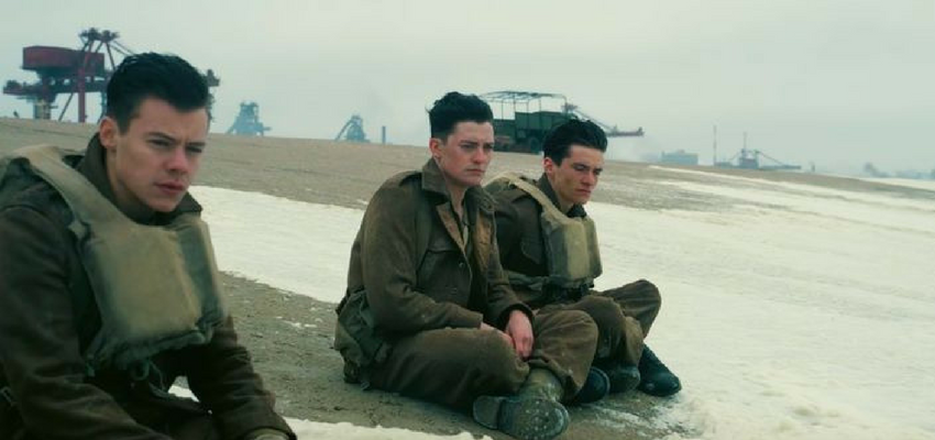Image of Dunkirk movie scene: soldiers sitting on a beach