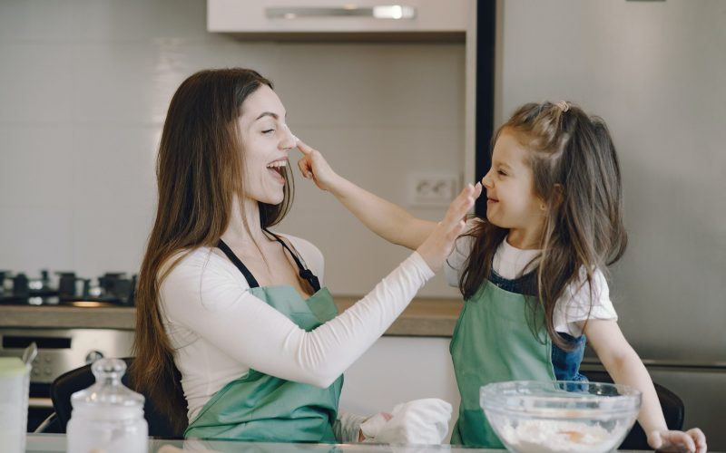 female babysitter baking with child